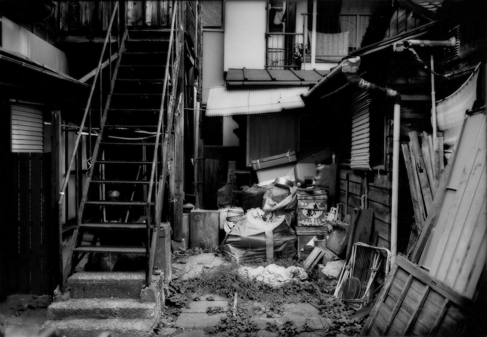 Privacy, Isolation / Cluttered garden reveals how an elderly couple is not able maintain the property without help any more. Dark, wooden homes, like theirs, in the style of the Showa Era (Emperor Hirohito's era) from the time immediate after the Second World War or before it, have been considered old and undesirable to Japanese families for a couple of decades.  It is by far the oldest house on the block.  Elderly people have died in Japan and not been found for extended periods of time in such dark houses not unlike this one, lacking gardens needing watering, accumulation of clutter or other obvious signs that someone might be seriously ill in the house.  Honmachii, Tokyo, Japan.