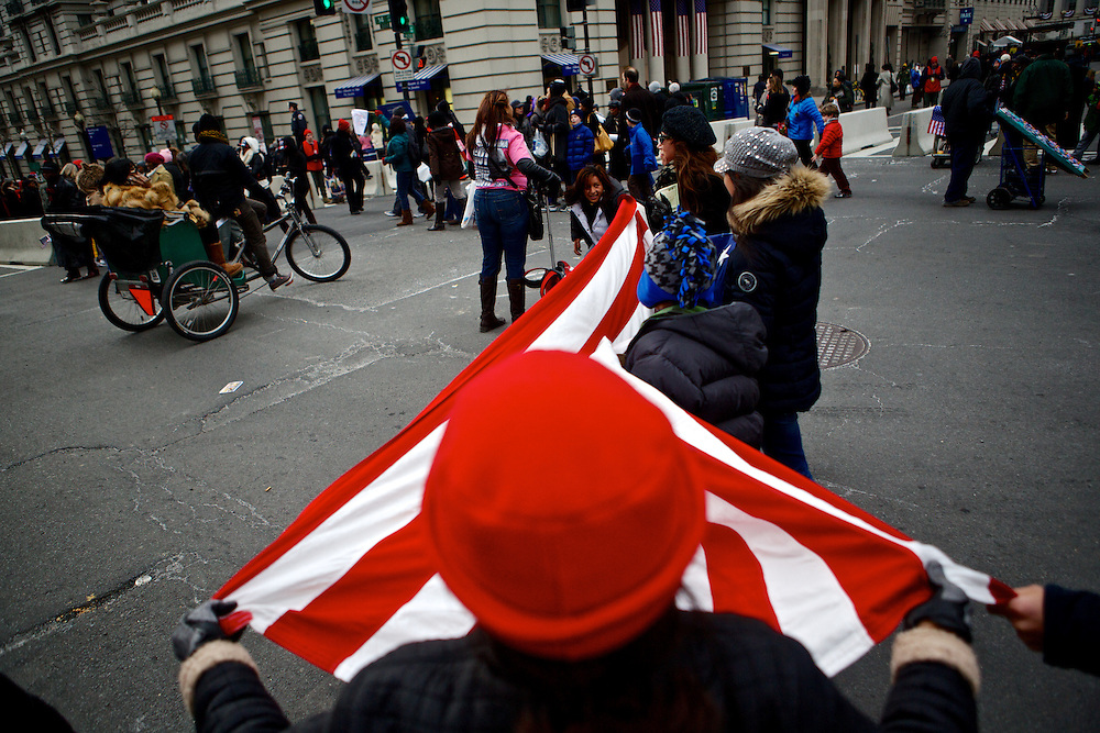 "Alida Yath, foreground, and her family arrive to the parade route with their own American flag before the inauguration parade for Pres. Barack Obama on January 21, 2013 in Washington, D.C. Yath, originally from Guatemala, became a U.S. citizen in August specifically so she could vote for Pres. Obama. ""I want better immigration laws, affordable education, health care and no more weapons,"" Yath said."