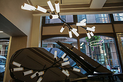 London, UK. 18 September, 2019. A limited edition Steinway Haara chandelier hangs above a Steinway piano in Steinway Hall, where Steinway & Sons have been based in London since 1875. Only ten pieces were produced as a collaboration celebrating craftsmanship between world renowned piano makers Steinway & Sons UK and bespoke sculptural lighting company Cameron Design House. Inspired by Steinway's iconic black lacquer gloss finish, it comes complete with beautiful brass accents and the iconic Steinway & Sons emblem.