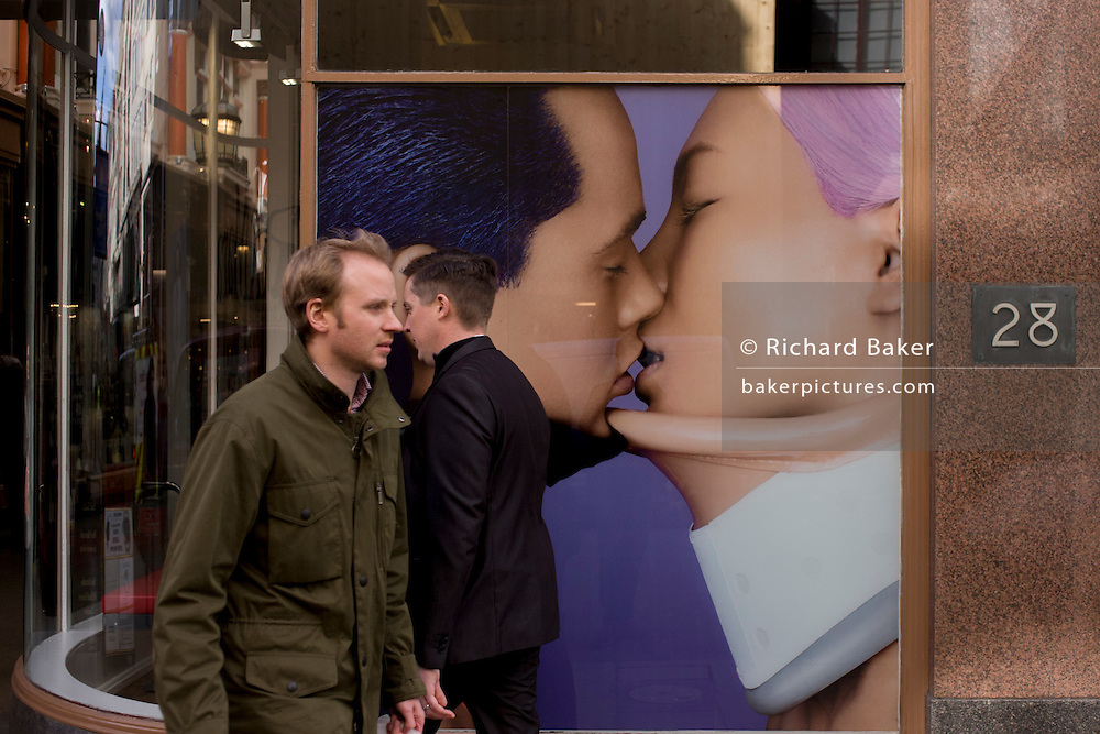 Londoners walk past a poster of a kissing couple for shoe retailer Camper in central London.