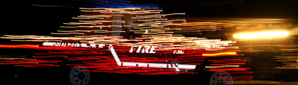 Fire vehicle with 911 emergency dial number shows in streaked lights of Cape May holiday parade
