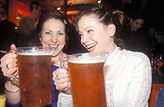 Two women laughing with big pints of beer, UK 2004