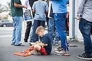 Tuulia Read, 6, of Santa Clara reads a comic book as others wait in line during Free Comic Book Day at Black Cat Comics in Milpitas, California, on May 6, 2017. (Stan Olszewski/SOSKIphoto)