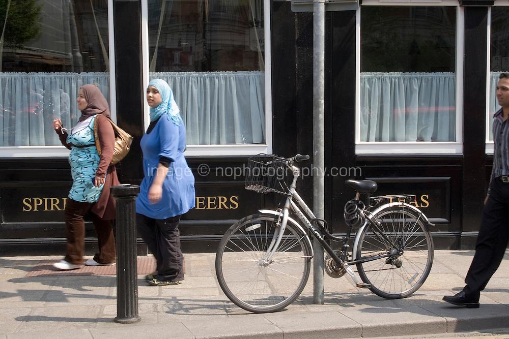 Two women in traditional headdress walking past a bar in Dublin Ireland