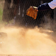 A young baseball player kicks up dust as he slides into third base during the Norwalk Little League baseball competition at Broad River Fields,  Norwalk, Connecticut. USA. Photo Tim Clayton