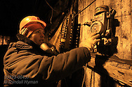 Woman uses Soviet-era cast-metal phone in monitoring rail cars that transport coal from mine shaft deep below Arktikugol offices; Barentsburg, Svalbard, Norway.