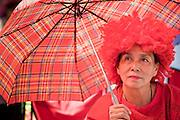 "09 MAY 2010 - BANGKOK, THAILAND: A Red Shirt woman in a red outfit and a red wig sits under a red umbrella at the Red Shirt rally in Bangkok Sunday. The Red Shirt leaders said Sunday they still conditionally supported the Prime Minister's ""Road Map to Reconciliation"" but that their opponents the Yellow Shirts needed to sign on to make the five point ""Road Map"" viable. About 5,000 people mostly from northeast Thailand, joined the Red Shirts in Ratchaprasong over the weekend. Members of the United Front of Democracy Against Dictatorship (UDD), also known as the ""Red Shirts"" and their supporters have occupied Ratchaprasong intersection, the site of Bangkok's fanciest shopping malls and several 5 star hotels, since April 4. The Red Shirts are demanding the resignation of current Thai Prime Minister Abhisit Vejjajiva and his government. The protest is a continuation of protests the Red Shirts have been holding across Thailand. They support former Prime Minister Thaksin Shinawatra, who was deposed in a coup in 2006 and went into exile rather than go to prison after being convicted on corruption charges. Thaksin is still enormously popular in rural Thailand.   PHOTO BY JACK KURTZ"