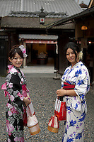 Two young women dressed in traditional Japanese Kimonos pose for the camera in Kyoto, Japan.