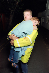 Young girl wrapped in blanket being carried by worker from emergency services,