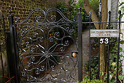 A decorative iron gate at the entry to a quiet garden.