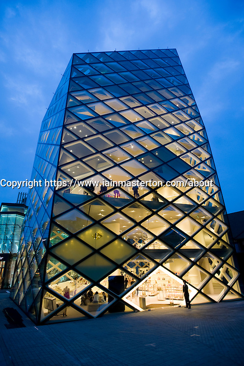 Evening view of spectacular glass walled Prada store in Aoyama Tokyo Japan