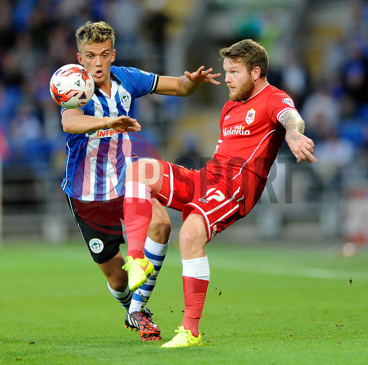 Wigan Athletic's Emyr Huws closes down Cardiff City's Aron Gunnarsson - Photo mandatory by-line: Dougie Allward/JMP - Mobile: 07966 386802 19/08/2014 - SPORT - FOOTBALL - Cardiff - Cardiff City Stadium - Cardiff City v Wigan Athletic - Sky Bet Championship