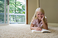 Portrait of girl (7-9) reading book on carpet smiling