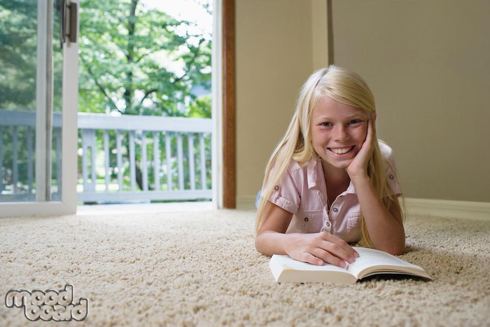 Portrait of girl (7-9) reading book on carpet smiling