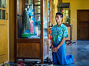 19 NOVEMBER 2017 - HWAMBI, YANGON REGION, MYANMAR:  A man kneels in the portico during mass at Sacred Heart's Catholic Church in Hwambi, about 90 minutes north of Yangon. More than 500 people attend mass at Sacred Heart's, and the sanctuary was full. Catholics in Myanmar are preparing for the visit of Pope Francis. He is coming to the Buddhist majority country November 27-30. There about 500,000 Catholics in Myanmar, about 1% of the population. Catholicism was originally brought to what is now Myanmar more than 500 years ago by Portuguese missionaries and traders.   PHOTO BY JACK KURTZ