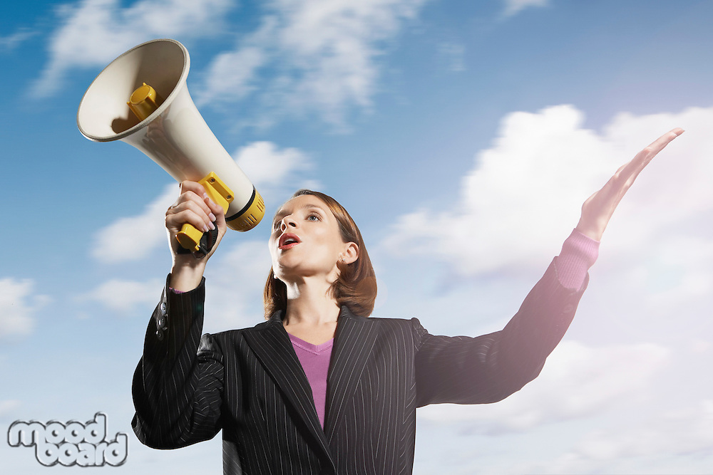 Mid-adult woman shouting through megaphone outside