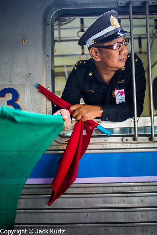 17 APRIL 2013 - BANGKOK, THAILAND: A conductor in a 3rd class train car signals that the train is about to leave the station in Hua Lamphong Train Station in Bangkok. Songkran, the traditional Thai New Year, is the busiest time of the year for Thai domestic travel. Many people in Bangkok return to their home provinces for the holiday and some people in the provinces travel to Bangkok for the holiday. Songkran, usually a three day holiday, was five days this year because the official days on the weekend. Trains and buses coming into Bangkok were reported to be fully booked and the State Railway of Thailand added extra trains and carriages to accommodate the crowds.    PHOTO BY JACK KURTZ