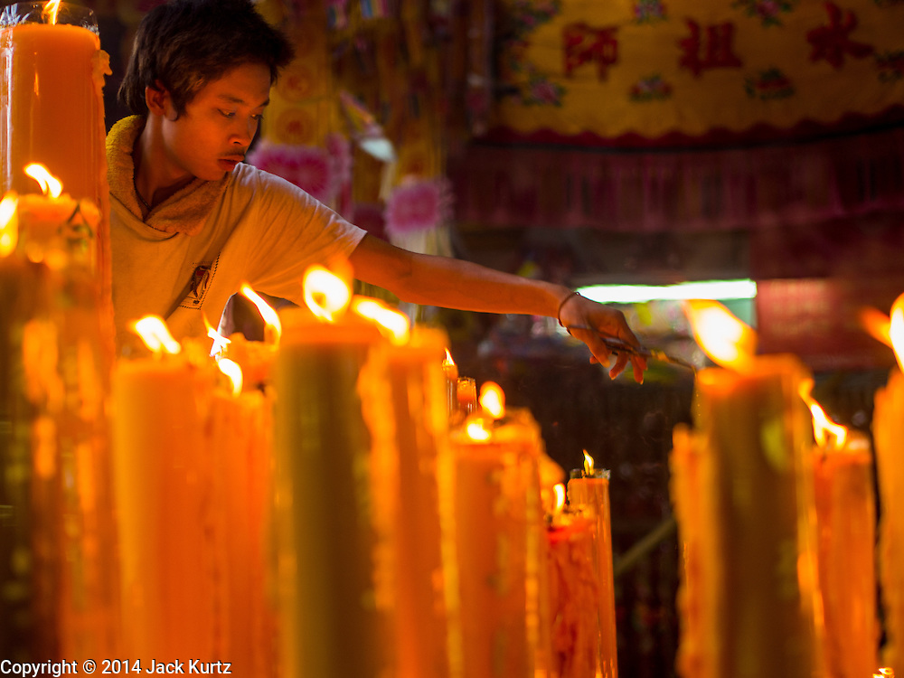 27 SEPTEMBER 2014 - BANGKOK, THAILAND: A temple attendant takes care of prayer candles during the celebration of the Vegetarian Festival at the Chow Su Kong Shrine in Talat Noi, a Chinese enclave in Bangkok. The Vegetarian Festival is celebrated throughout Thailand. It is the Thai version of the The Nine Emperor Gods Festival, a nine-day Taoist celebration beginning on the eve of 9th lunar month of the Chinese calendar. During a period of nine days, those who are participating in the festival dress all in white and abstain from eating meat, poultry, seafood, and dairy products. Vendors and proprietors of restaurants indicate that vegetarian food is for sale by putting a yellow flag out with Thai characters for meatless written on it in red.    PHOTO BY JACK KURTZ