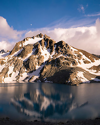 A brief respite from the incessant Patagonian wind allowed for a partial reflection of Cerro Madsen on Laguna de los Tres at sunrise.   Laguna de los Tres was named for the original party of 3 to successfully summit Mount FitzRoy which lies to the west of the glacier fed lake.