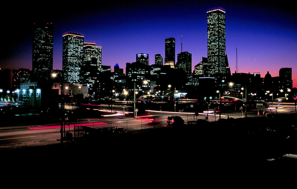 Night traffic passing the silhouetted Houston, Texas skyline at night.