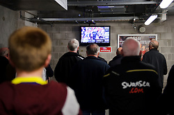 Swansea supporters watch the crunch Liverpool v Manchester City tie on TV screens before their match kicks off - Photo mandatory by-line: Rogan Thomson/JMP - 07966 386802 - 13/04/2014 - SPORT - FOOTBALL - Liberty Stadium, Swansea -  Swansea City v Chelsea FC - Barclays Premier League.