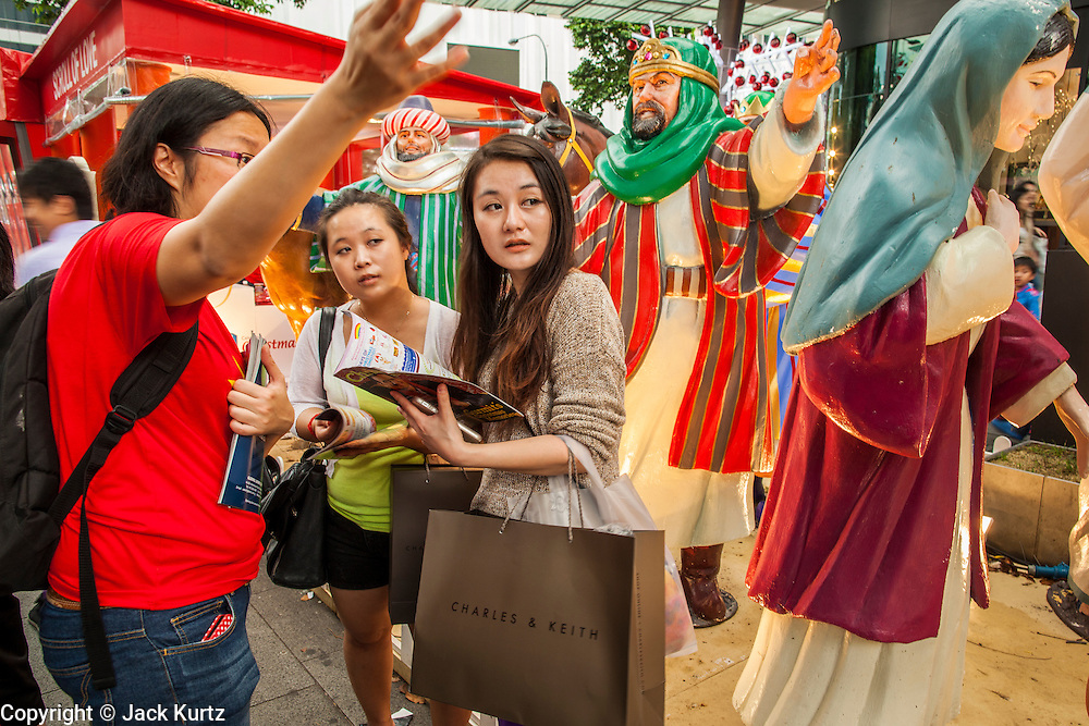 "22 DECEMBER 2012 - SINGAPORE, SINGAPORE:  A volunteer helps shoppers near a nativity scene during ""Christmas on a Great Street"" on Orchard Rd in Singapore. Businesses on Orchard Road, Singapore's famed shopping street, sponsors the annual event. The street is decorated with holiday lights, stores stay open late and crowds pack the area. This is the 8th year Singapore has held the ""Christmas on a Great Street"" event.   PHOTO BY JACK KURTZ"