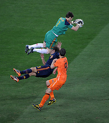 Iker CASILLAS collects the ball whilst Carles PUYOL defends and  Robin VAN PERSIE looks on  during the 2010 FIFA World Cup South Africa  Final match between Holland and Spain at Soccer City  on 11 July, 2010 in Johannesburg, South Africa.