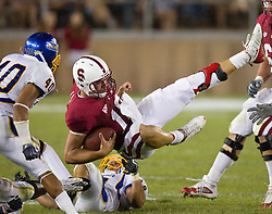 September 19, 2009; Stanford, CA, USA;  Stanford Cardinal quarterback Andrew Luck (12) is tackled by San Jose State Spartans linebacker Travis Jones (14)in the fourth quarter of the game at Stanford Stadium. Stanford defeated San Jose State 42-17.