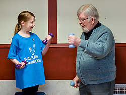Pictured: Abby McConnell takes part in one of the exercises with Ronnie Downie from Burnside.<br /> <br /> A young fundraiser inspired by comedian Billy Connolly's battle with Parkinson's  prepares for a charity walk on April 15th - World Parkinson's Day - to raise funds for the charity. Abby McConnell (7) from Mount Florida met sufferers and took part in a seated exercise class specially designed for sufferers of the disease at Rutherglen West Parish Church in Glasgow.<br /> <br /> © Dave Johnston / EEm
