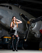 Attractive young fashion model poses with bag by vintage aeroplane.