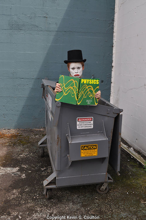 "Humorous photograph of a mime in a garbage dumpster reading a physics text book visually depicting the saying ""A mime (mind) is a terrible things to waste!"""