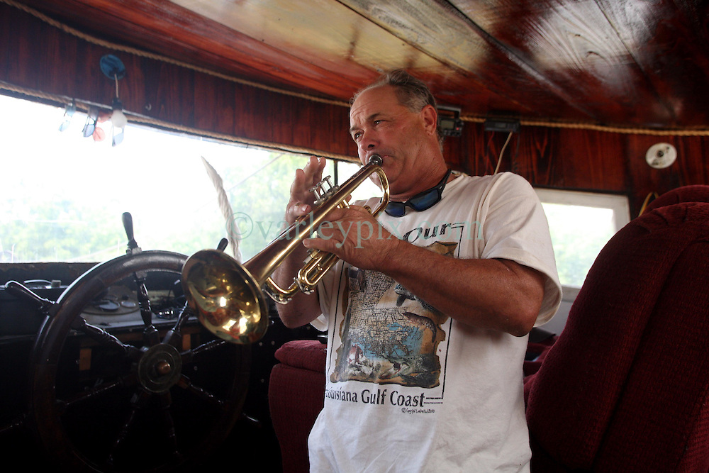10 June 2010. Breton Sound Marina, Hopedale, Louisiana. USA.  <br /> Ricky Robin, captain of the boat 'Lil Rick.,' plays his trumpet in the wheel house. Robin, a commercial fisherman since he was a teenager is now subcontracted to BP. Robin awaits equipment to be loaded onto his shrimp boat which has been converted to an oil skimming vessel. Robin doubts how effective the equipment will be and suggests BP should leave such work to the professionals.<br /> The ecological and economic impact of BP's oil spill is devastating to the region. Oil from the Deepwater Horizon catastrophe is evading booms laid out to stop it thanks in part to the dispersants which means the oil travels at every depth of the Gulf and washes ashore wherever the current carries it. The Louisiana wetlands produce over 30% of America's seafood and oil and gas production. They are the most fertile wetlands and nurseries of their kind in the world. BP's oil is killing everything.<br /> Photo; Charlie Varley/varleypix.com