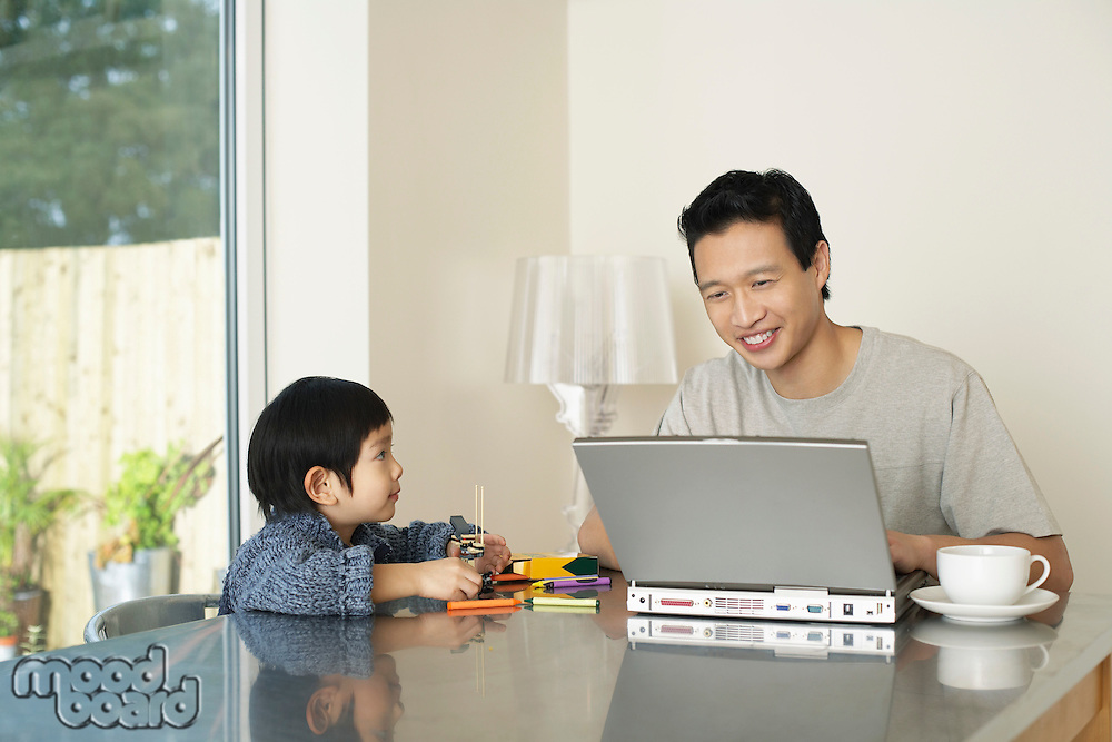 Father and son sitting at kitchen table Father working on computer