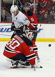 February 8, 2008; Newark, NJ, USA;  Anaheim Ducks left wing Chris Kunitz (14) and New Jersey Devils defenseman Colin White (5) battle for the rebound after a save by New Jersey Devils goalie Martin Brodeur (30) during the third period at the Prudential Center in Newark, NJ. The Anaheim Ducks defeated the New Jersey Devils by a 2-1 margin.