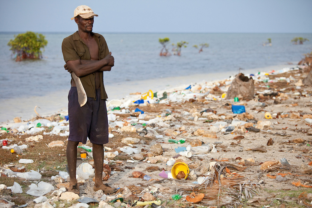 A man with machete stands on a beach littered with trash on the north coast of Ile de la Gonave, Haiti