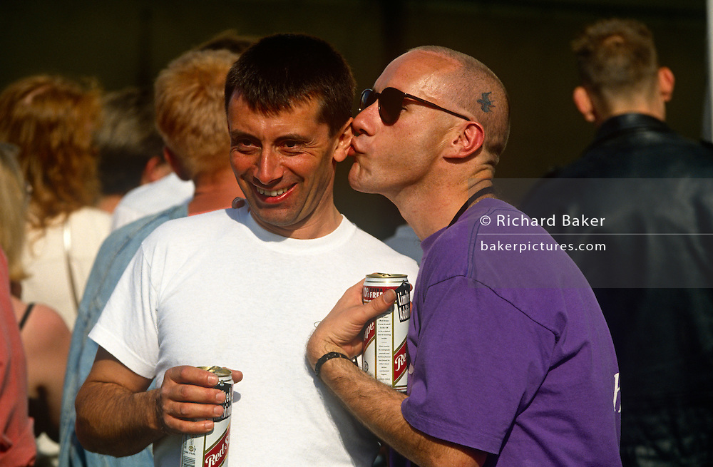 Two men enjoy the party athmosphere at a Gay Pride event, one kissing the other's ear as a joke.
