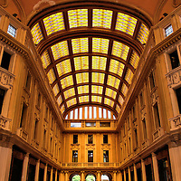 Interior of Galleria Vittorio Emanuele III in Messina, Italy <br /> In 1929, the Palace of the Gallery was sponsored by the General Electric Company of Sicily and designed to become &ldquo;the center of city life &hellip; day and night&rdquo; with offices, shops, cafes and residences. The interior of Galleria Vittorio Emanuele III is best described as warm, rich and ornately appointed with mosaic floors and a golden hue created by the stained-glass canopy. In 2000, it was declared to be an artistic and historic site.