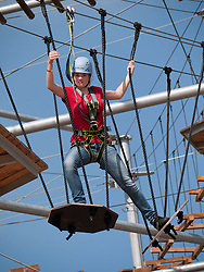Young woman climbing on new outdoor adventure playground featuring multi-level climbing and obstacle courses in Berlin Germany