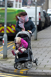 © Licensed to London News Pictures. 8/02/2016. Porthcawl, Bridgend, Wales, UK.A young woman with achild in a buggy gets blasted by the wind in the town. People struggle to stay on their feet in winds gusting over approximately 60mph. Storm Imogen batters the small Welsh seaside resort of Porthcawl in the county borough of Bridgend on the South coast of Wales, UK. Photo credit: Graham M. Lawrence/LNP