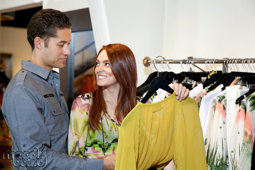 Happy woman with boyfriend looking at each other in fashion clothing boutique