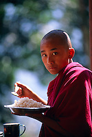 Young novice monk eating lunch, Tibetan Chorten and Monastery, Gangtok, Sikkim, India