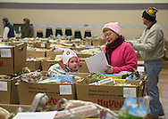 Grace Bruns (from left), 5, of Fairfax and Sue Berger of Cedar Rapids look over an address list of boxes they will deliver as the Society of St. Vincent de Paul delivers 237 holiday meals to families in Cedar Rapids, Marion, and Hiawatha from the St. Wenceslaus Church gym at 1230 5th St SE in Cedar Rapids on Saturday morning, December 22, 2012. (Stephen Mally/Freelance)
