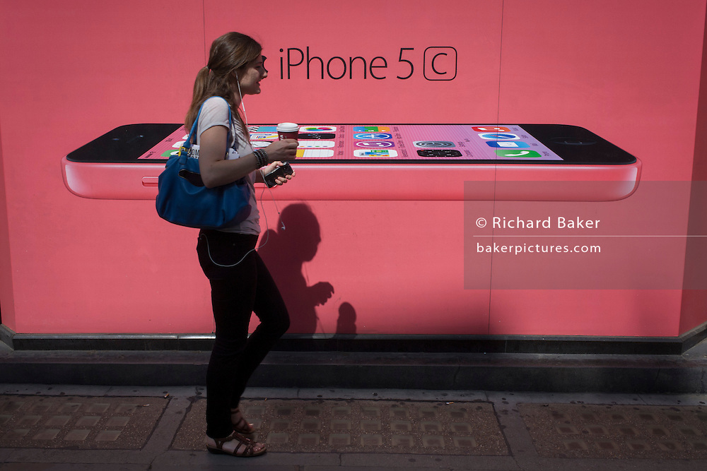 A woman walks past a phone network supplier's ad for the Apple iPhone 5c