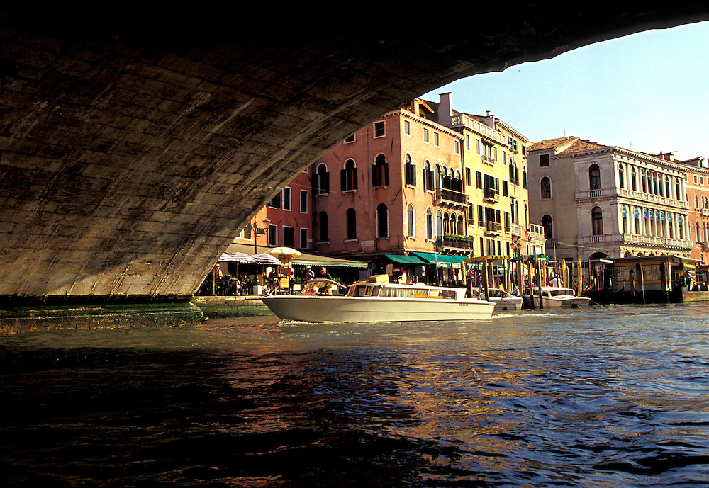 Venice, Italy:  A private launch cruises the Grand Canal and passes under the Rialto Bridge.