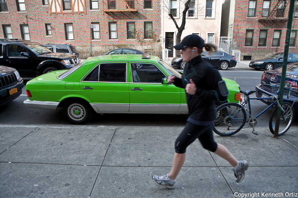 A jogger takes her morning run down 34th Avenue in Astoria and passes a lime green Mercedez-Benz.