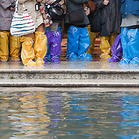 Tourist in Sant Mark Square with protecting boots on a day of exceptional High Tide in Venice with water above 140cm covering more than 50% ot town Marco Secchi /xianpix<br /> msecchi@gmail.com