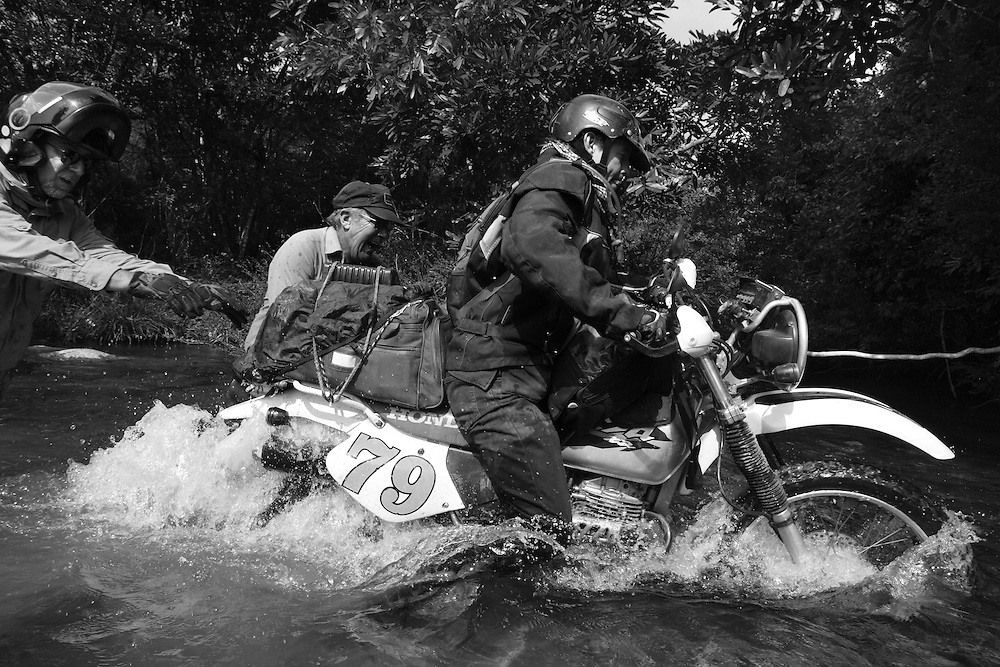 Billy (L) and Nol (C) help Steve traverse a stream along the Ho Chi Minh Trail, Laos.