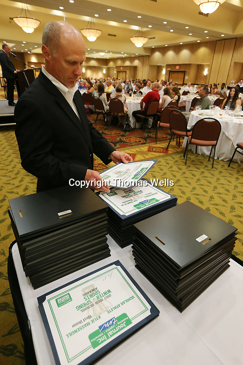 Northeast Mississippi Daily Journal General Manager Danny Smith gets the next award ready to be passed out during Monday's Winter & Spring Sport Banquest at the BancorpSouth Conference Center.