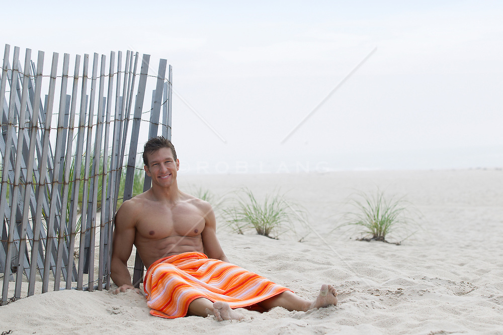 shirtless sexy man sitting against a beach fence in Southampton, NY