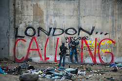 """© Licensed to London News Pictures. 23/01/2016. Calais, France. A man takes a picture of defaced Banksy artwork  surrounded by graffiti reading """"LONODN CALLING""""  at the entrance to the camp known as the 'Jungle' in Calais, France, where thousands of migrants and refugees attempting to reach the UK are currently living. Photo credit: Ben Cawthra/LNP"""
